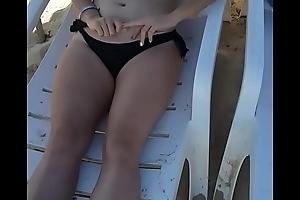 Hermana topless tomando sol en la playa